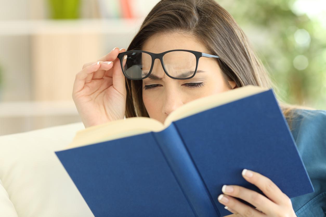 Woman suffering eyestrain reading a book
