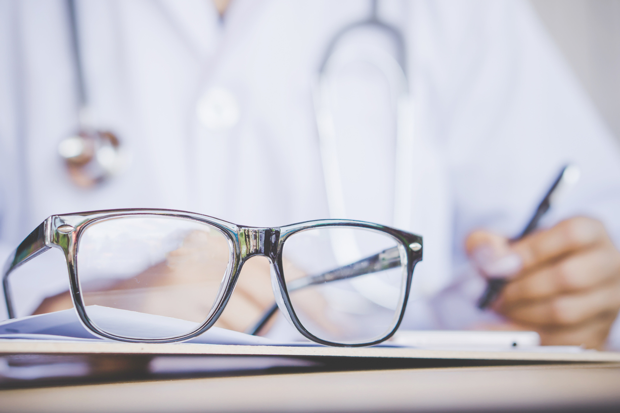 eye glasses on desk with blur background of doctor writing prescription