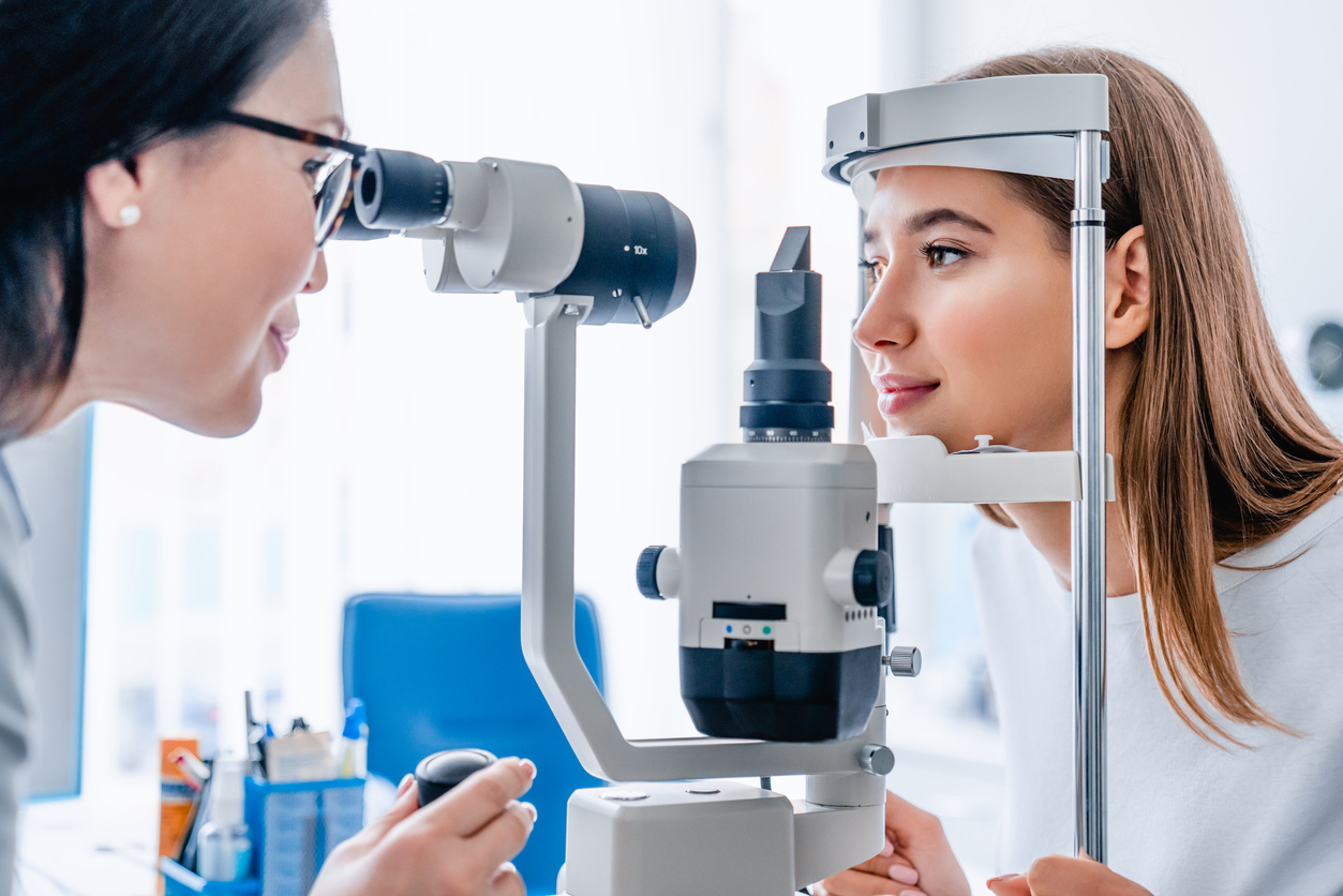 Side view shot of female doctor and patient in ophthalmology clinic