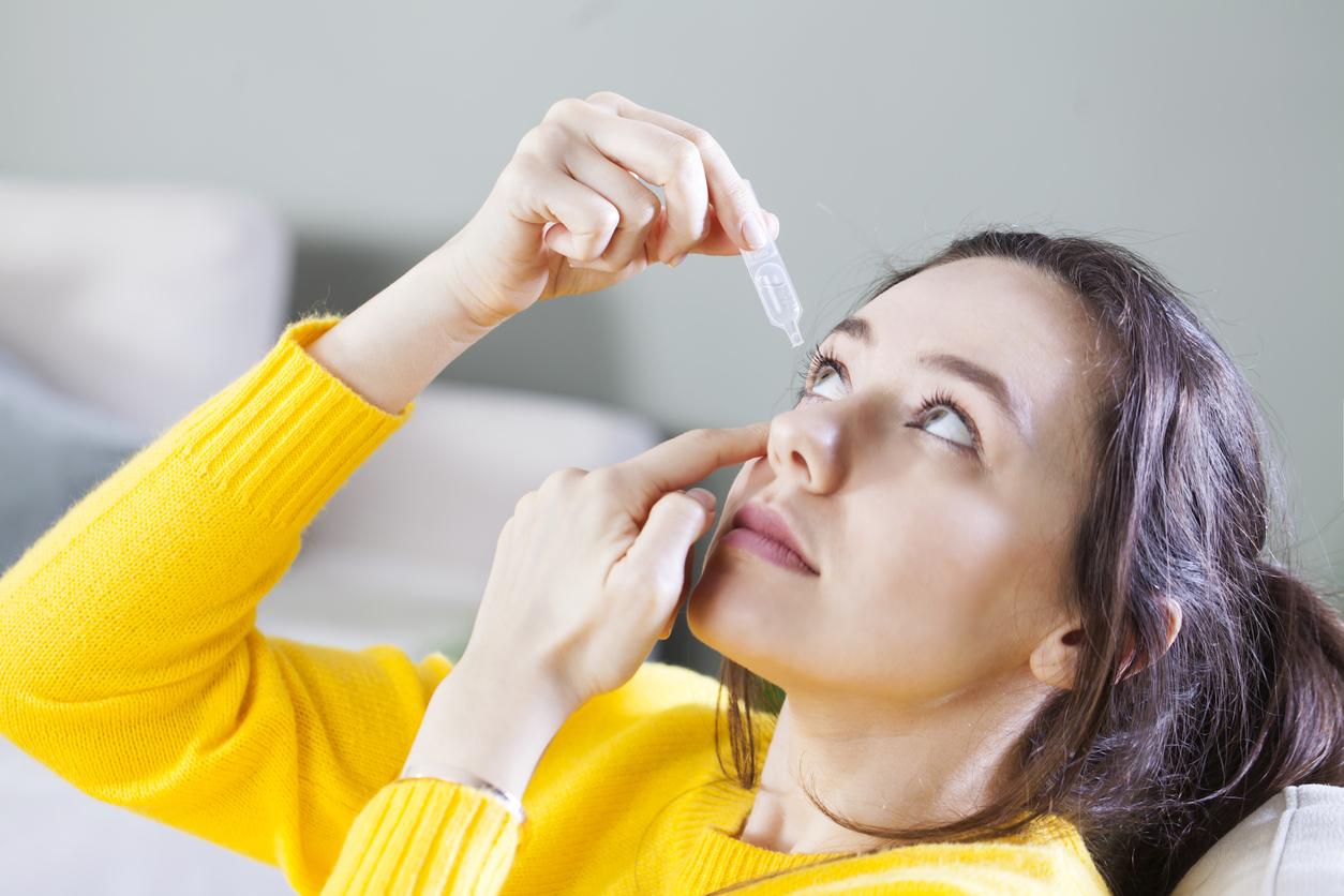 Closeup view of young woman applying eye drop, artificial tears.