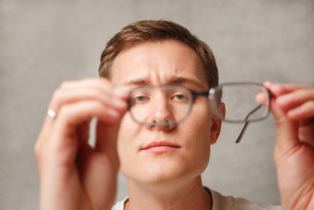 the young man holds glasses with diopter lenses and looks through them, the problem of myopia